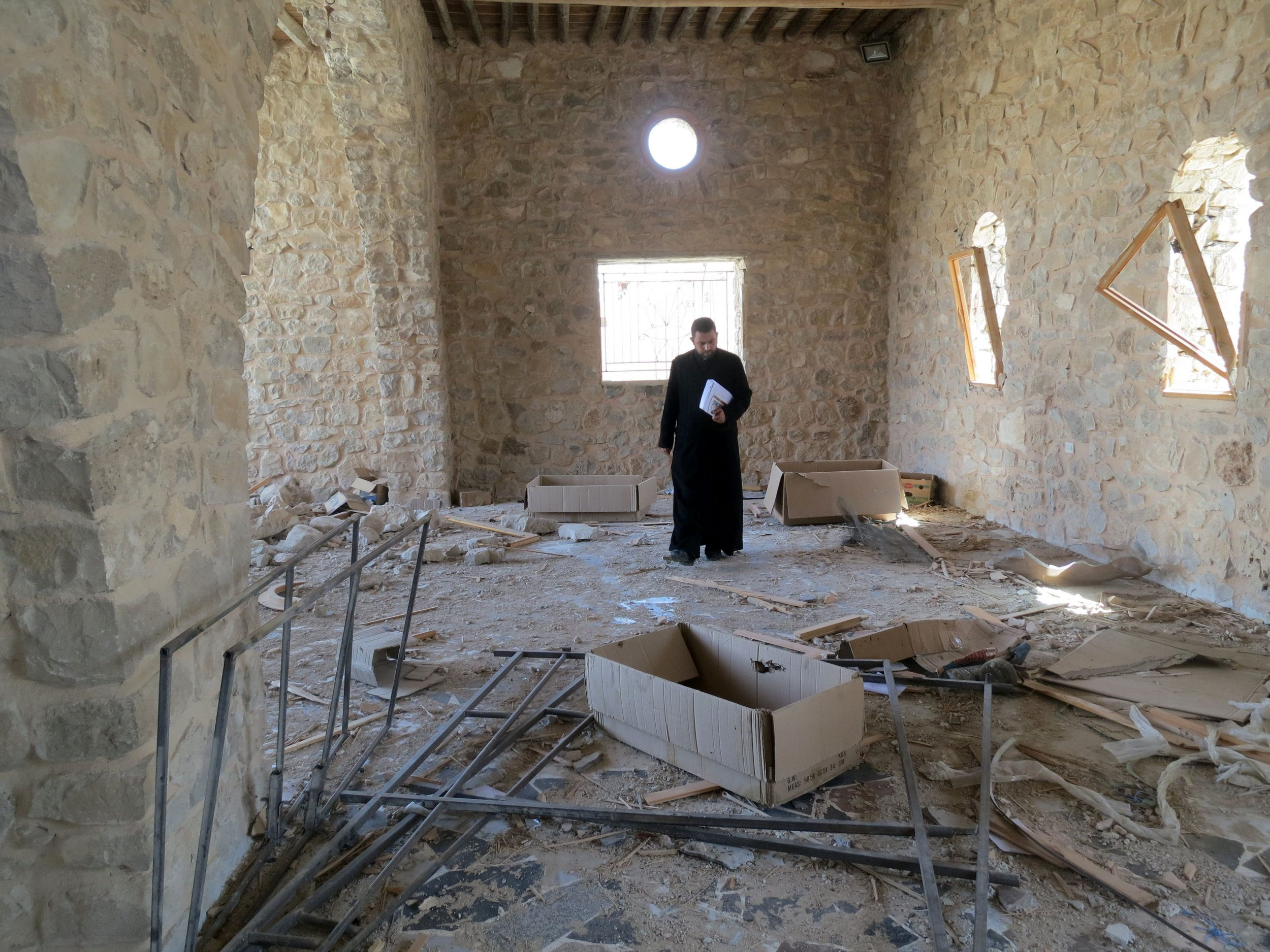 A Catholic priest inspects the damage at Mar Elian monastery in Al-Qaryatain.