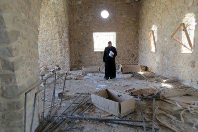 A Catholic priest inspects the damage at Mar Elian monastery in Al-Qaryatain.