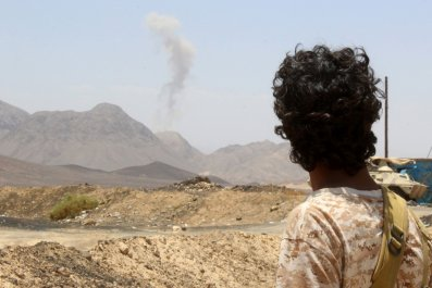 A Yemeni fighter loyal to the exiled president looks at rising smoke.