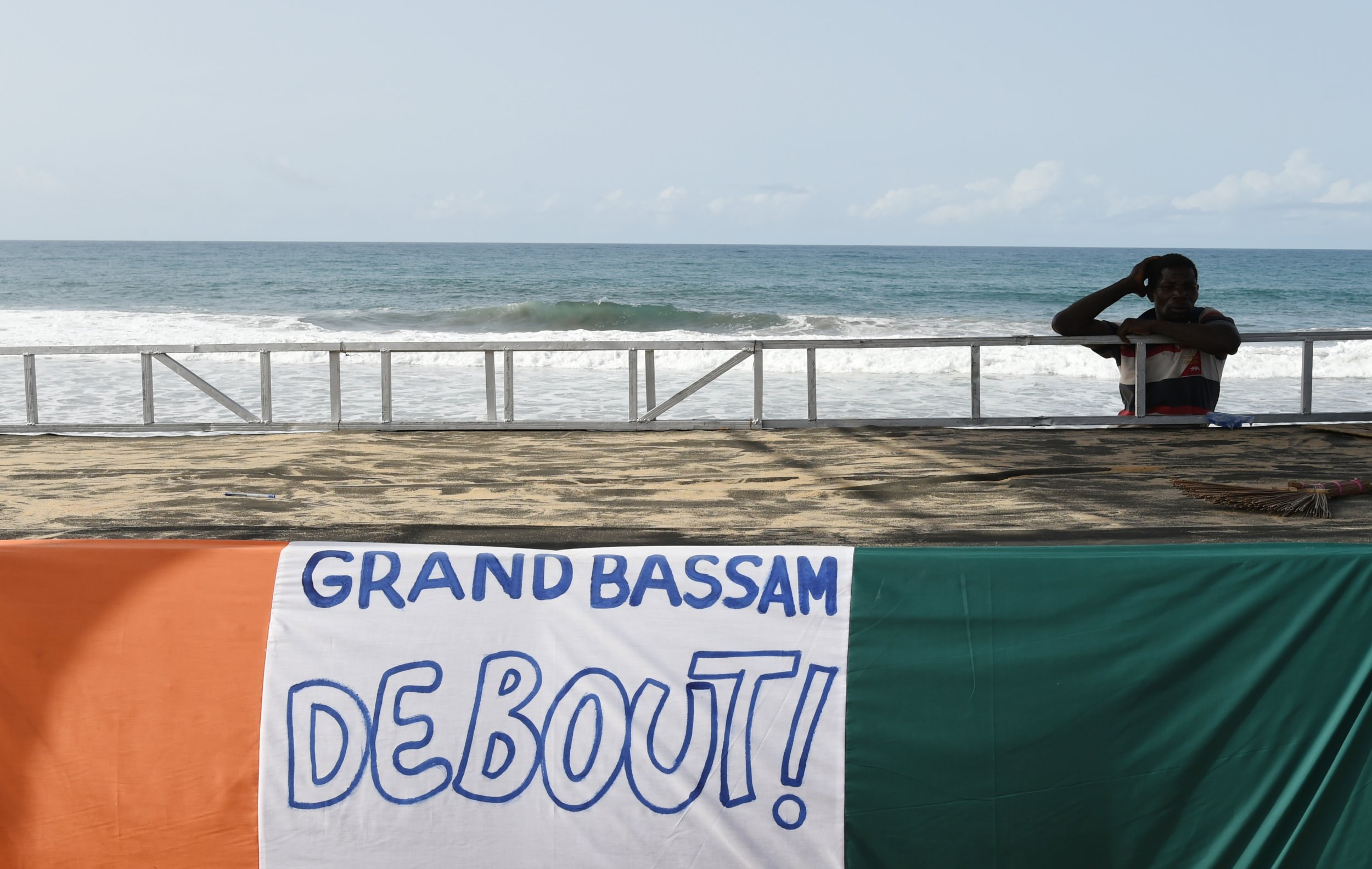 An Ivorian man stands near a Grand Bassam banner after an Al-Qaeda attack.
