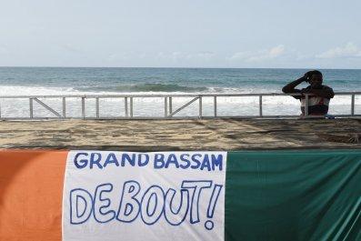 An Ivorian man stands near a Grand Bassam banner after an Al-Qaeda attack.