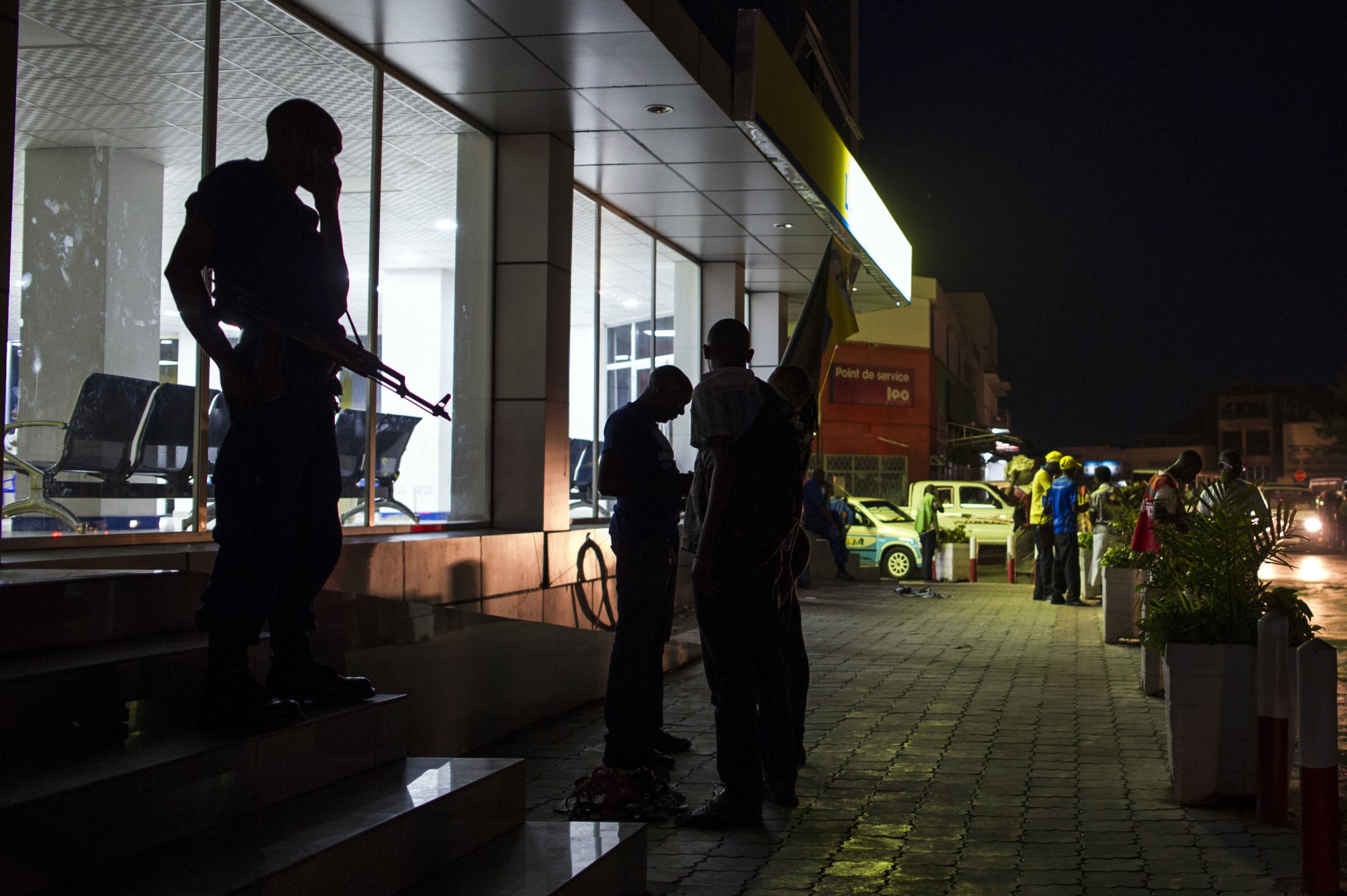 A Burundian policeman listens for news after the elections in Bujumbura.