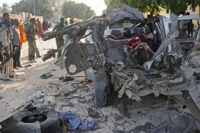 Somali soldiers and residents look at the site of an Al-Shabab car bomb in Mogadishu.