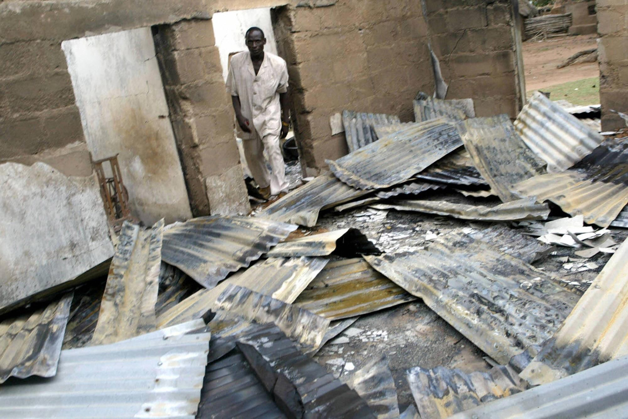 A pastor surveys a church destroyed by Fulani herdsmen in Plateau state.