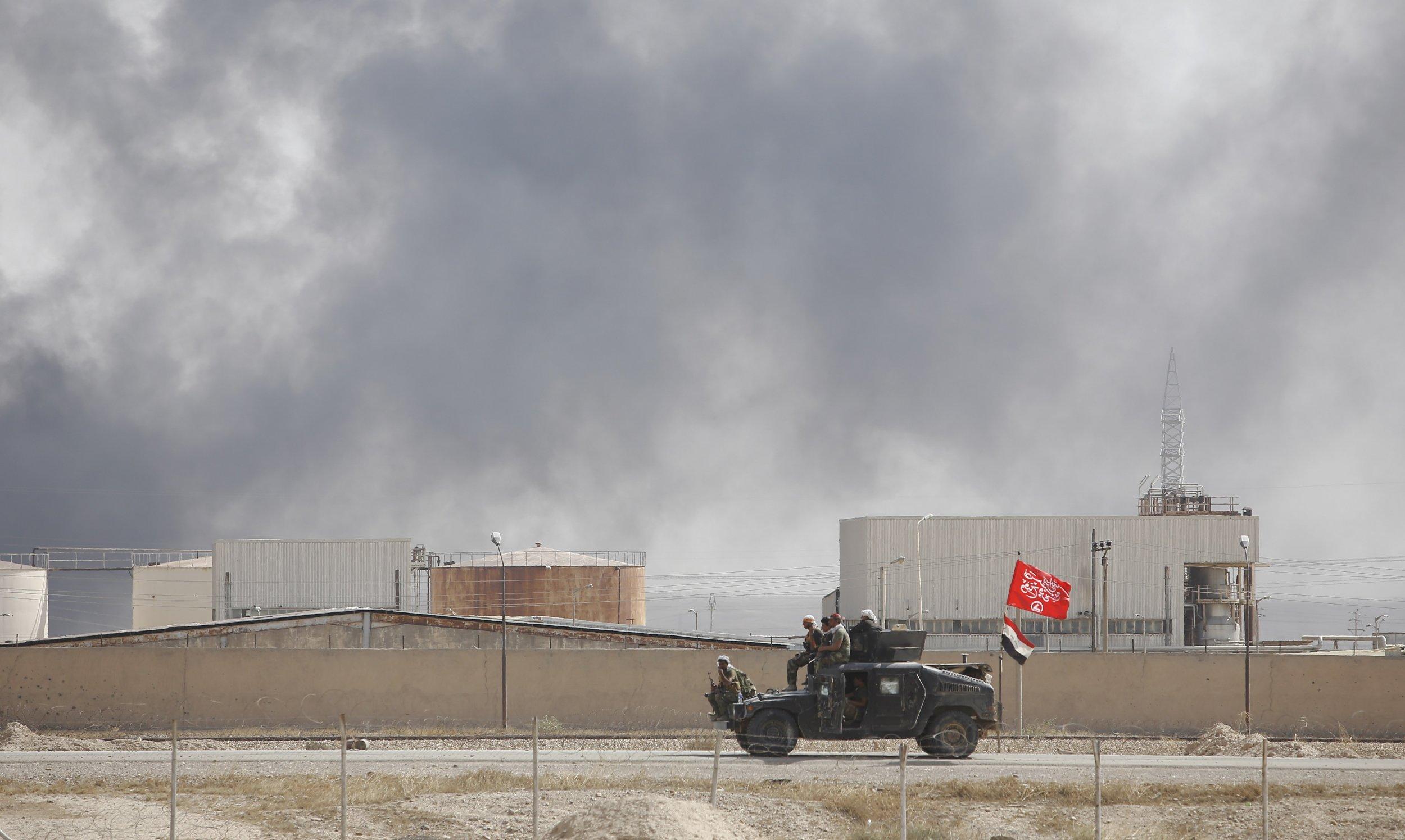 Iraqi fighters drive past oil refinery.