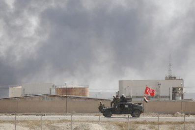 Iraqi fighters drive past oil refinery.