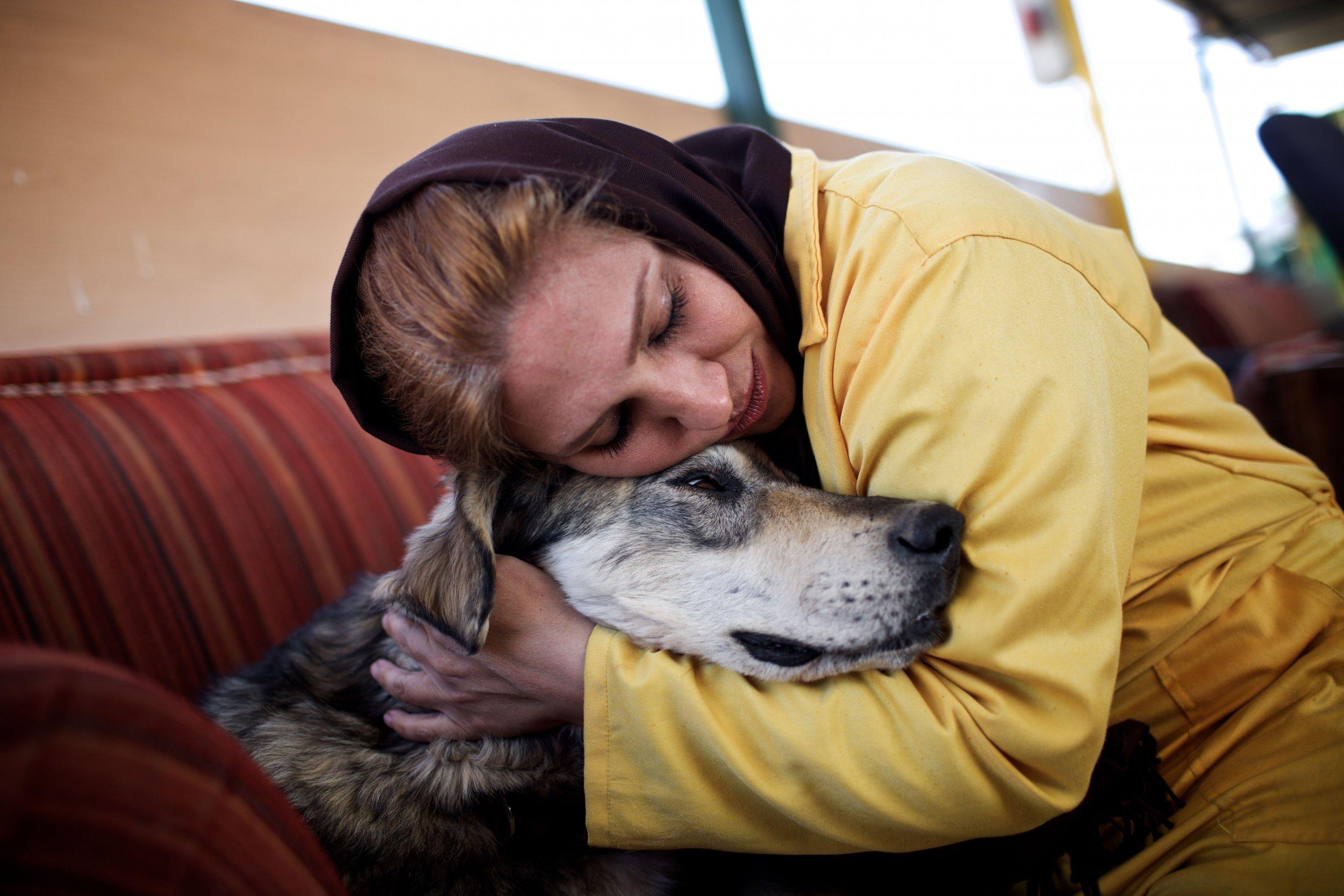 Iranian volunteer hugs dog.