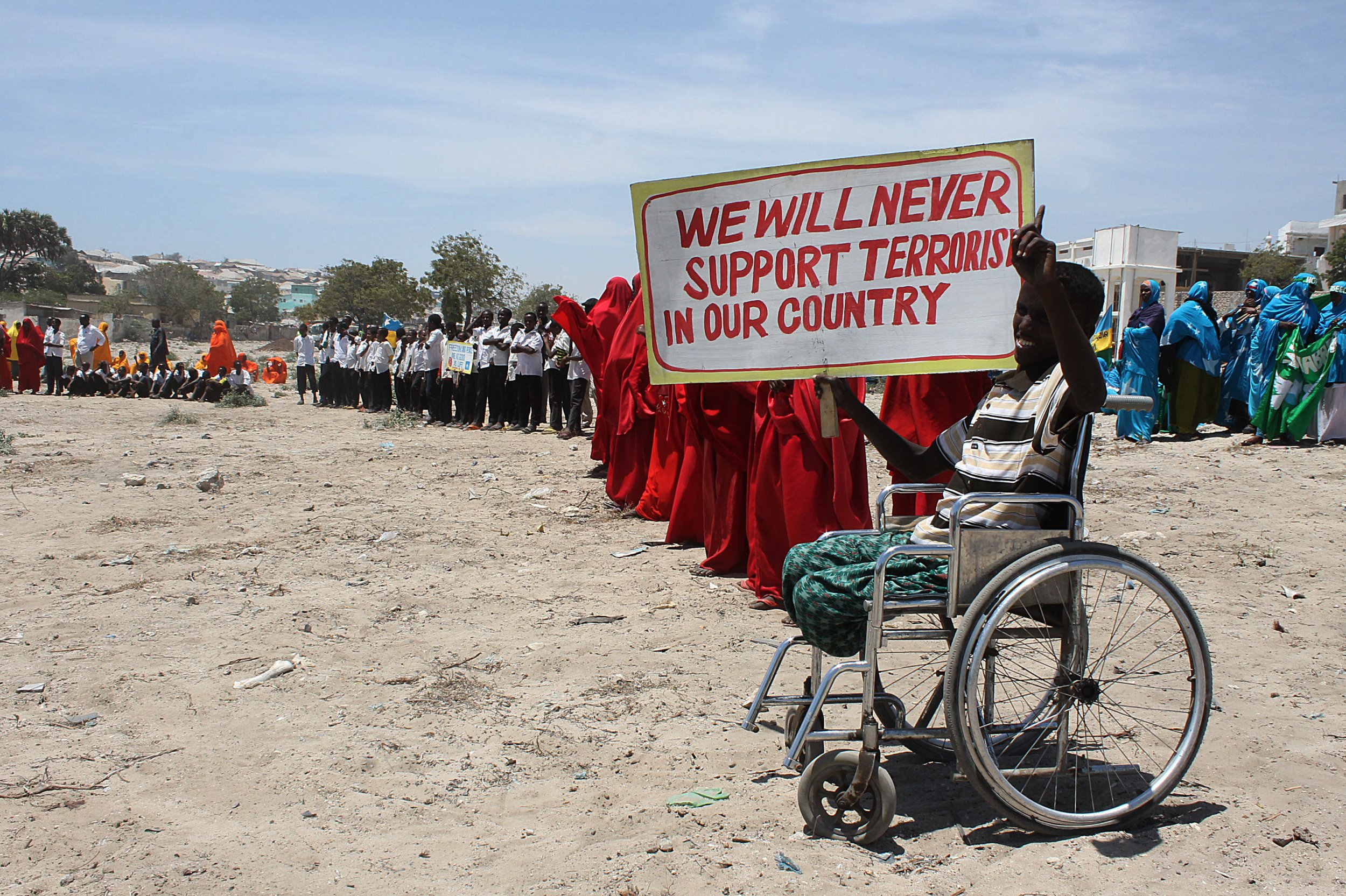 Disabled Somali boy with anti Al-Shabab poster.
