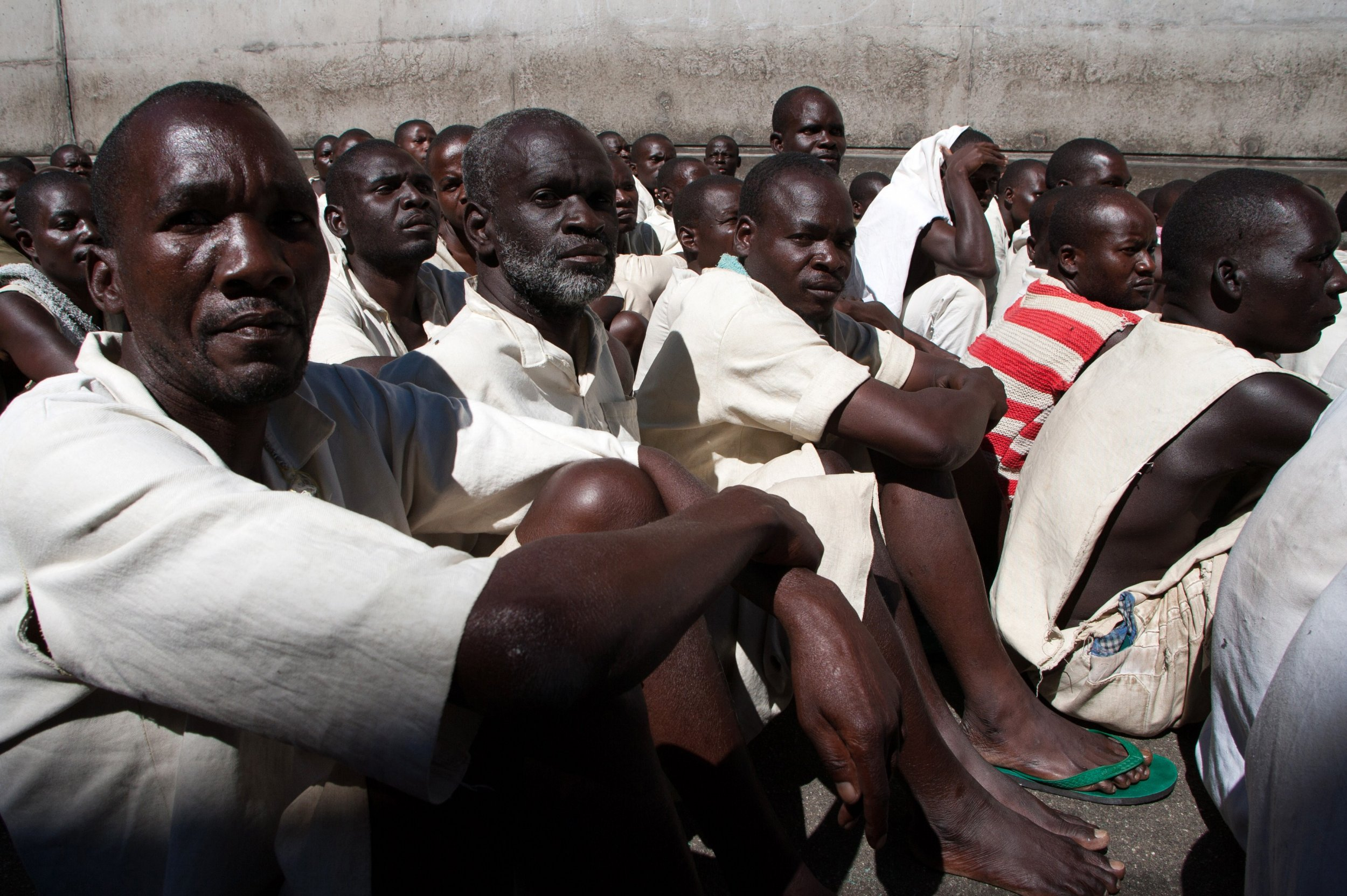 Zimbabwe prisoners sit in yard.