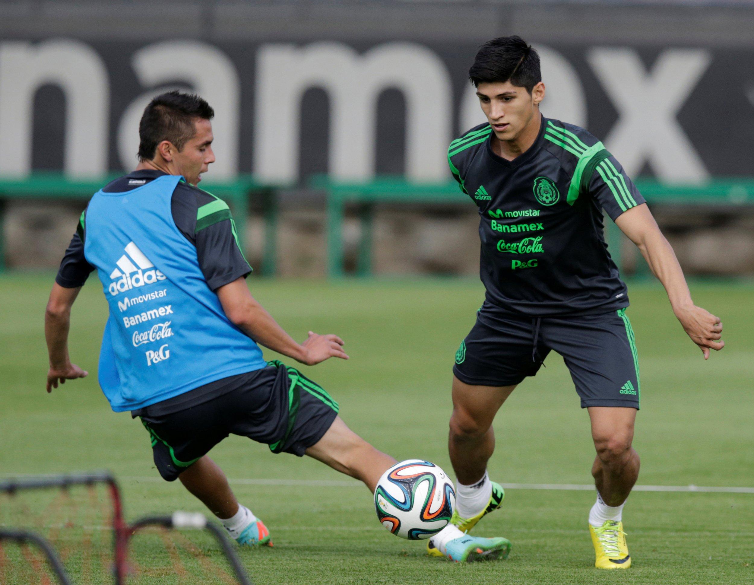 Mexico striker Alan Pulido dribbles past teammate.