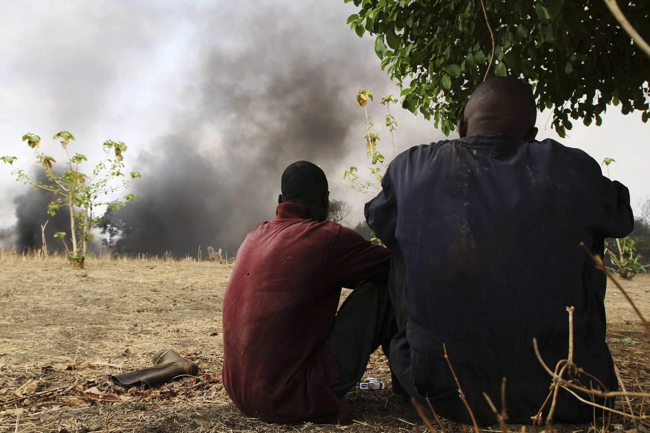 Workers in the Niger Delta watch a pipeline fire