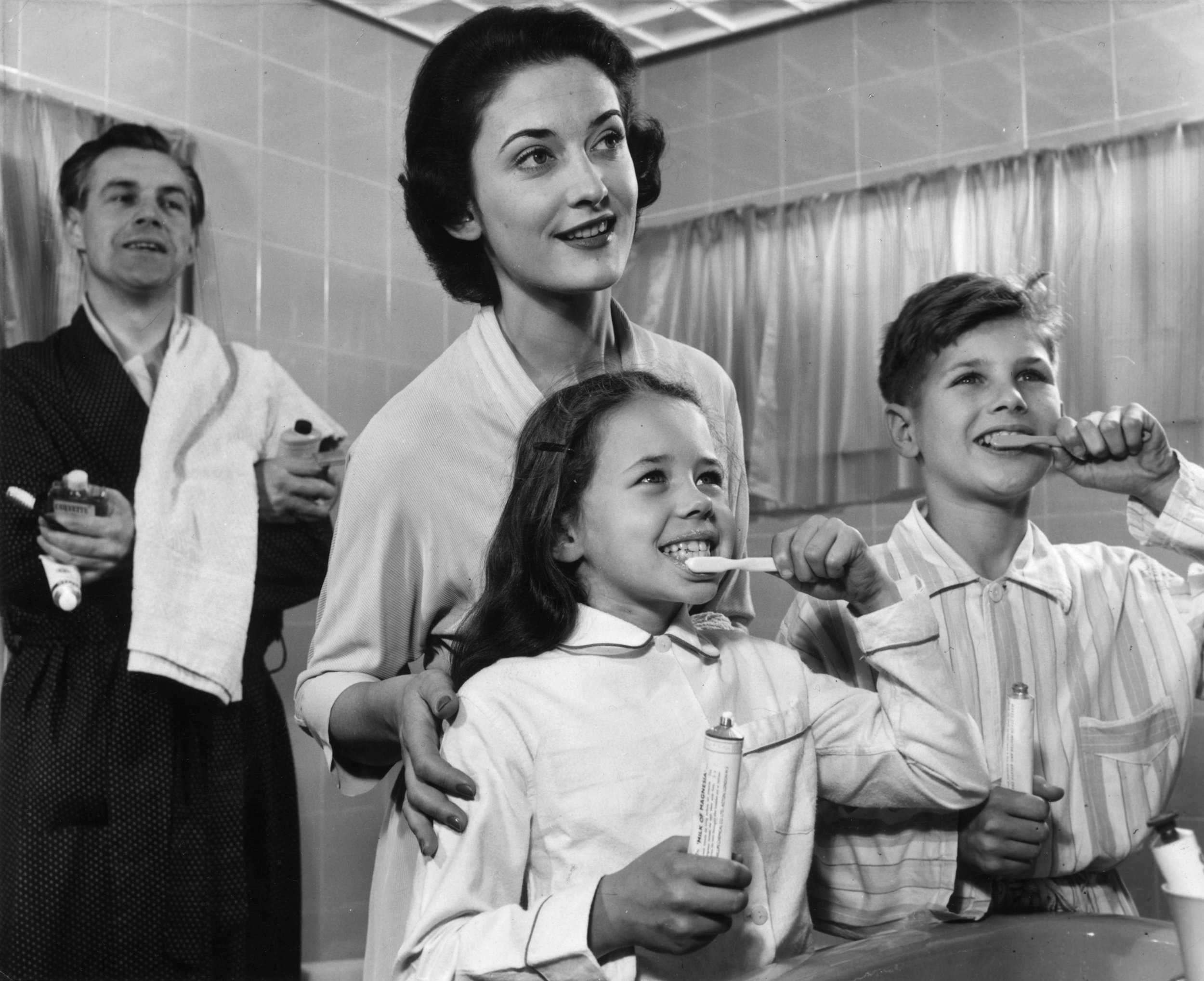 A family cleaning their teeth, circa 1955