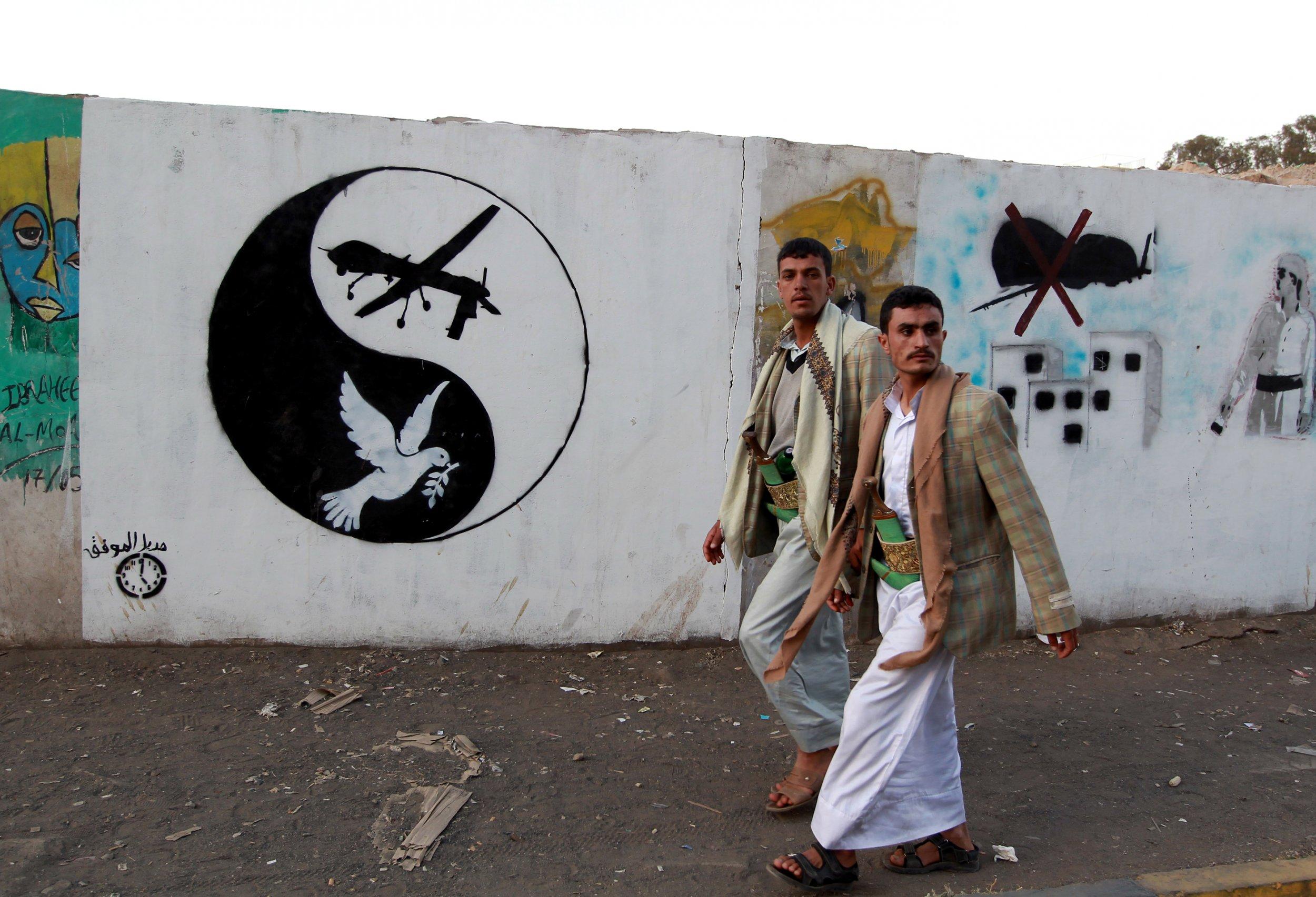 Yemeni man walks past drone art in Yemen