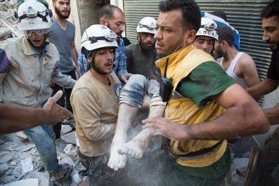 White Helmets rescue a body from rubble in Aleppo