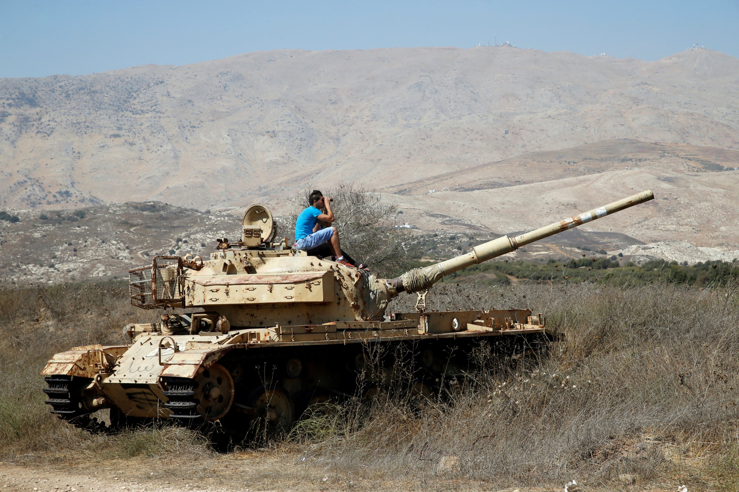 A man on a tank watching Syrian fighting