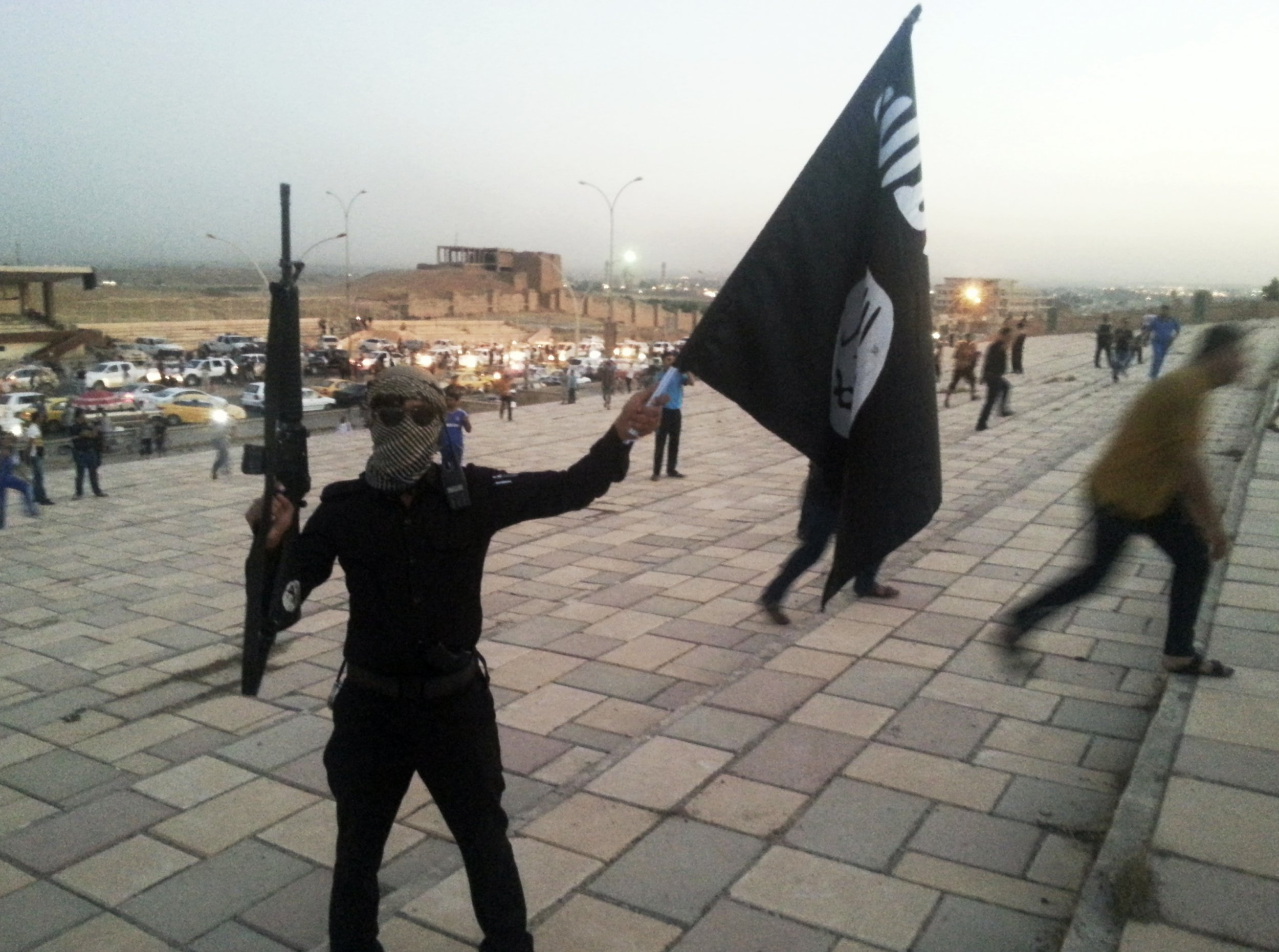 An Islamic State fighter waves the group's flag