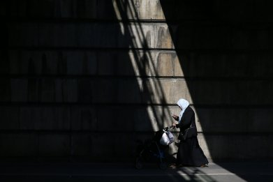 A Muslim woman pushes a pushchair