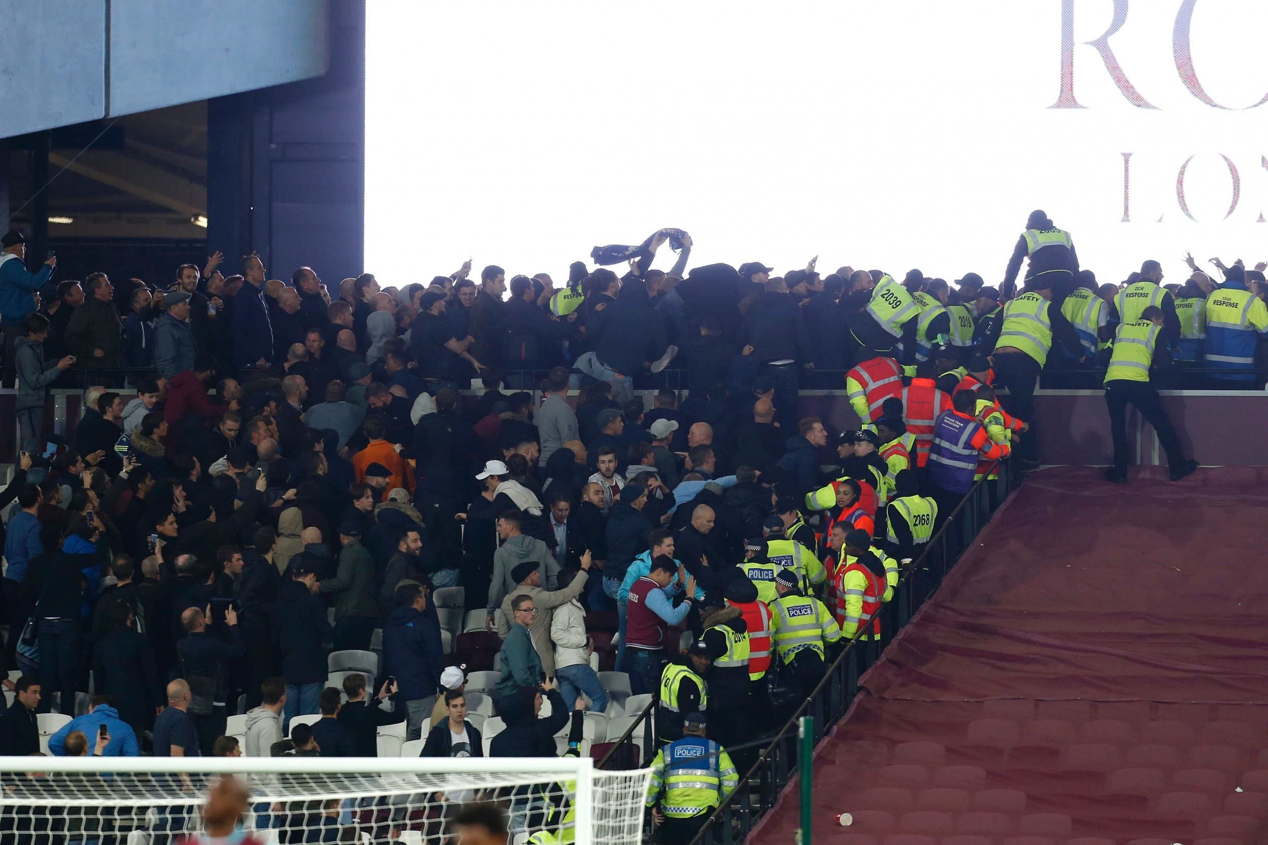 Police and stewards try to separate West Ham United and Chelsea supporters.