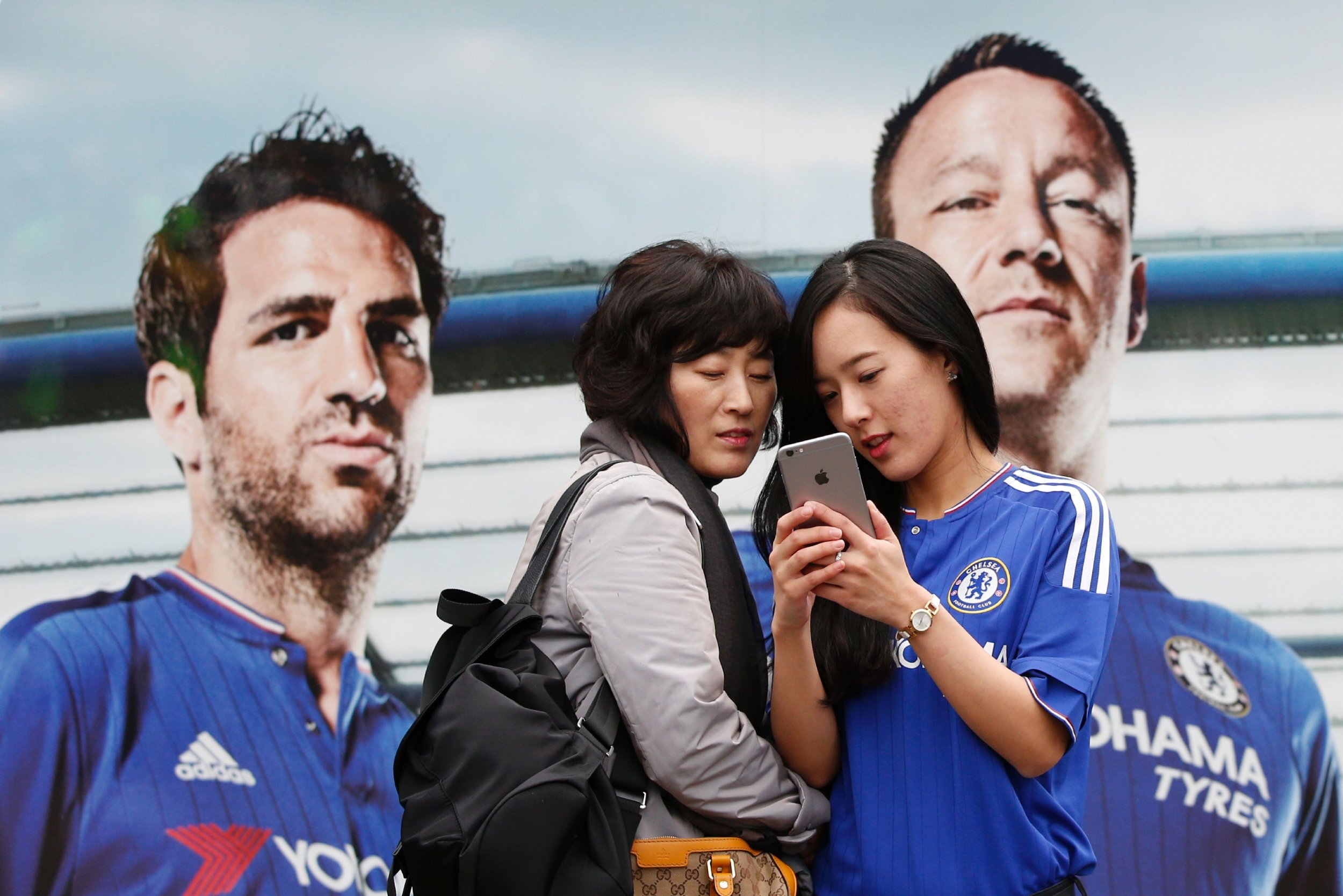 A poster at Stamford Bridge showing Cesc Fabregas, left.