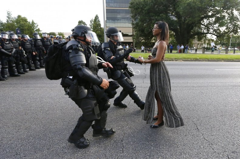 A protester stands before three police officers