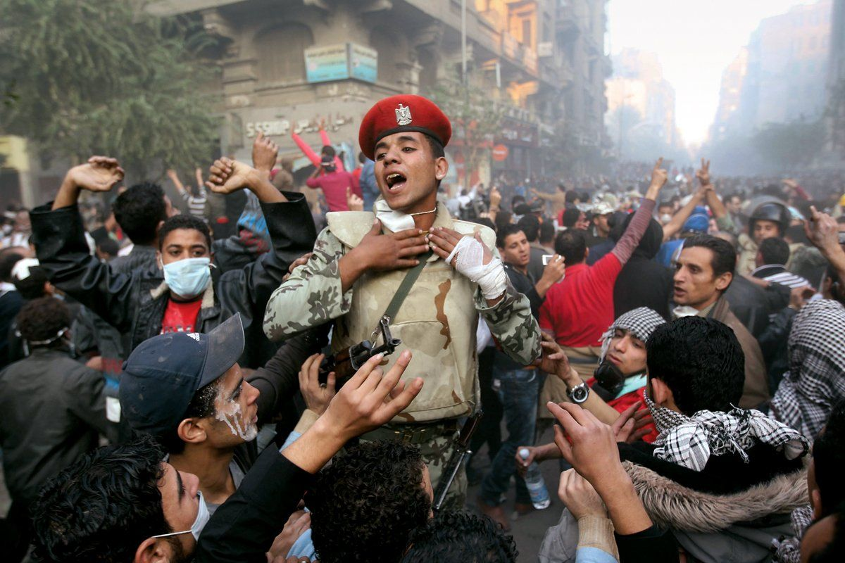 A soldier tries to separate protesters from riot police in Tahrir Square.