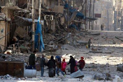 Syrians walk over rubble in Aleppo