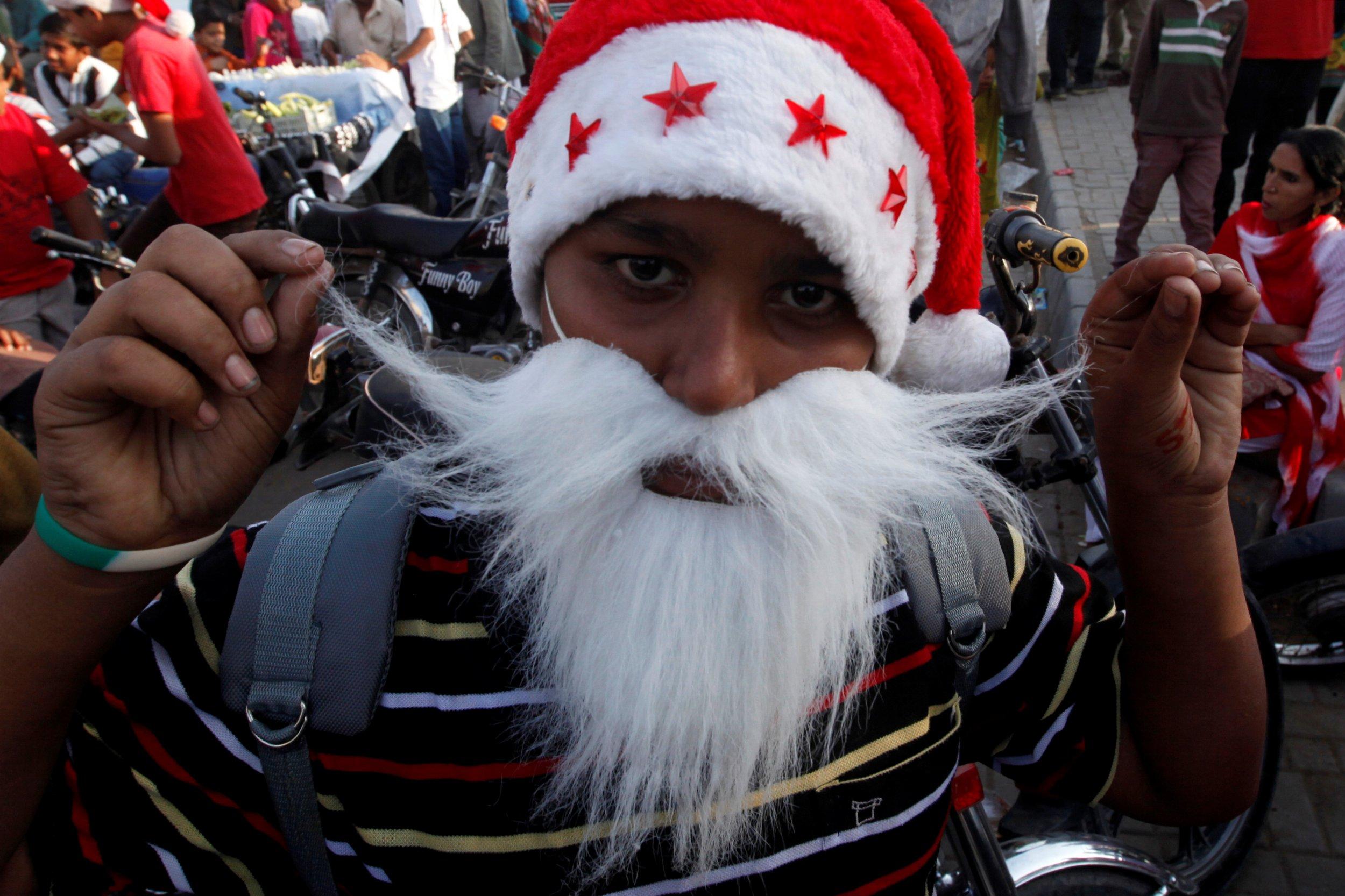 A boy wears Santa Claus' hat and beard