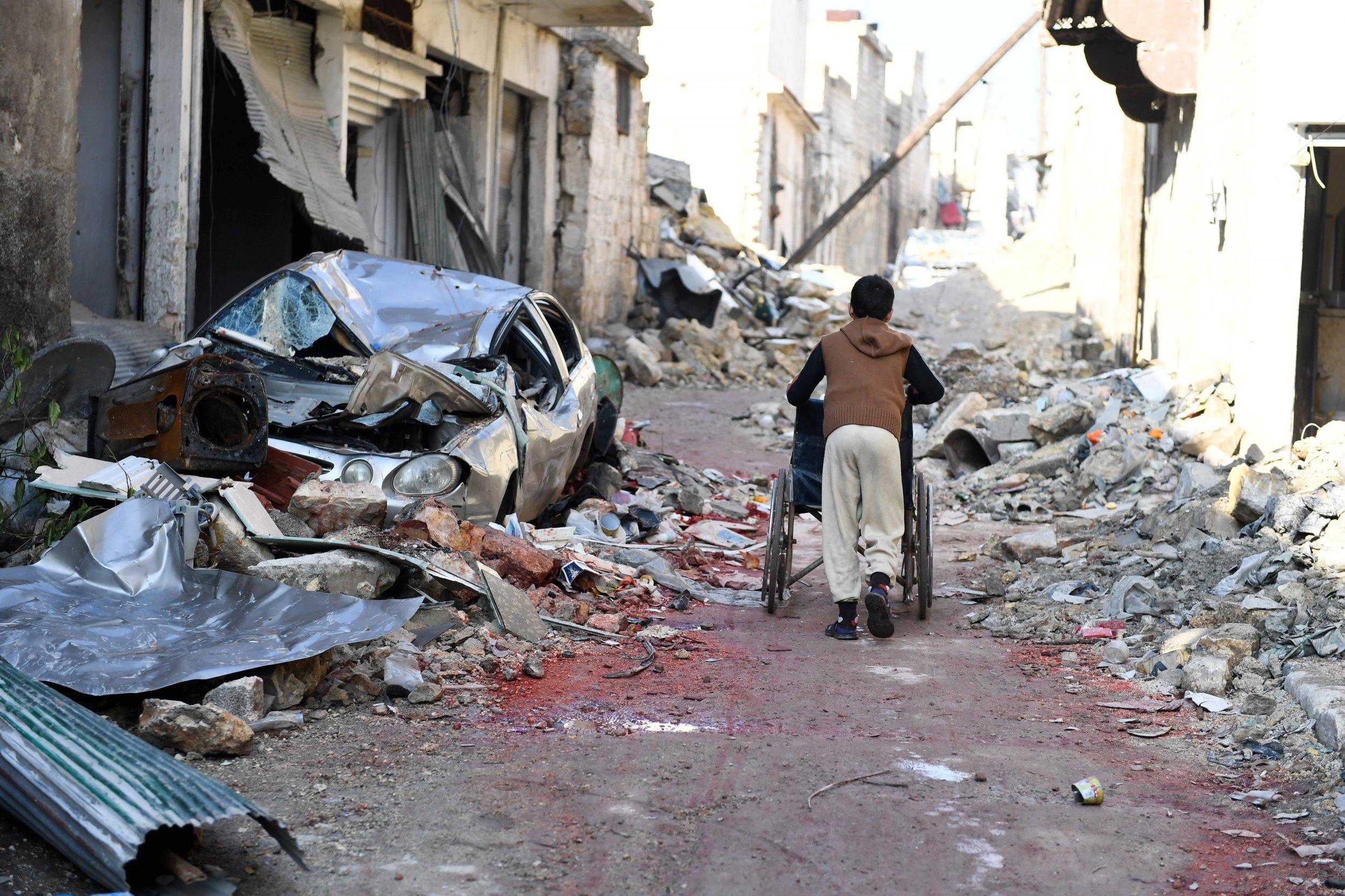 Aleppo boy pushing wheelchair