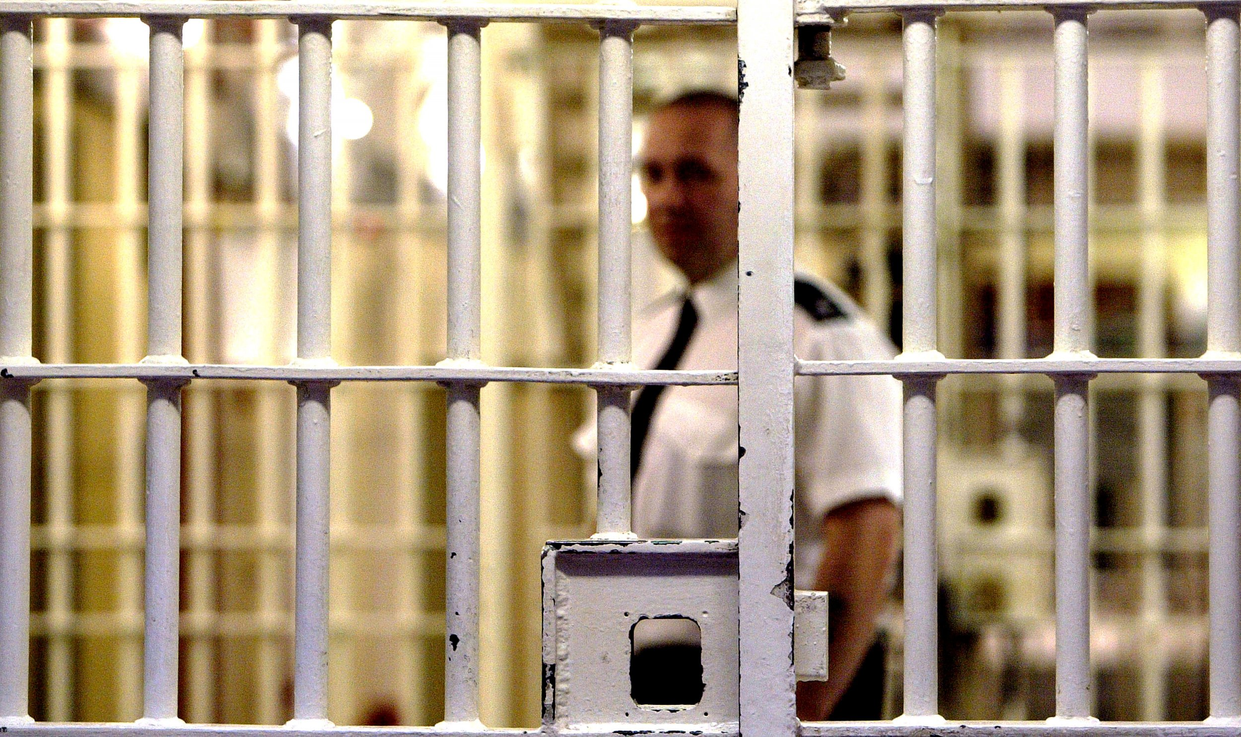A prison warden stands in front of a cell