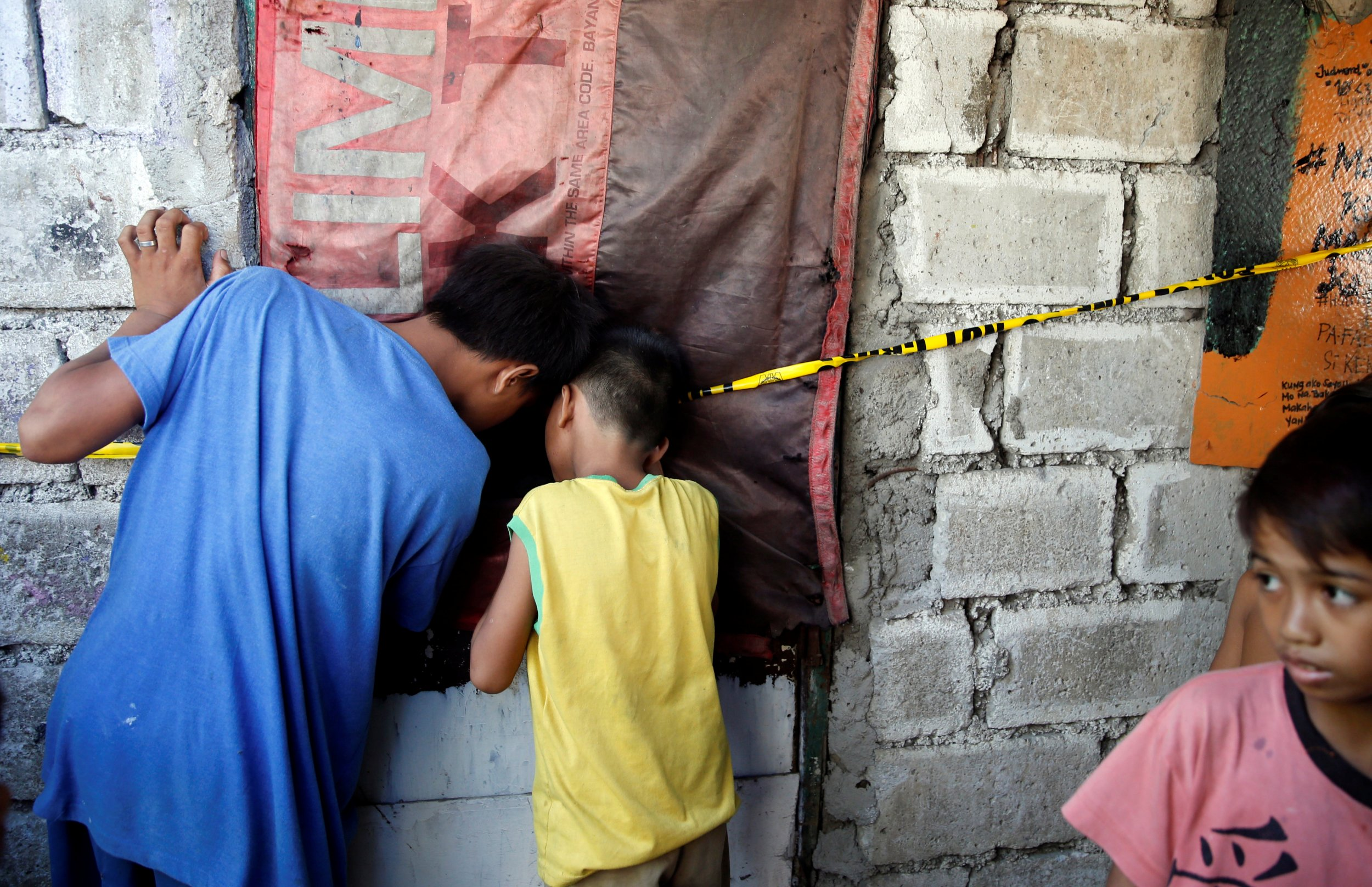 Children look at dead people through hole in drug war