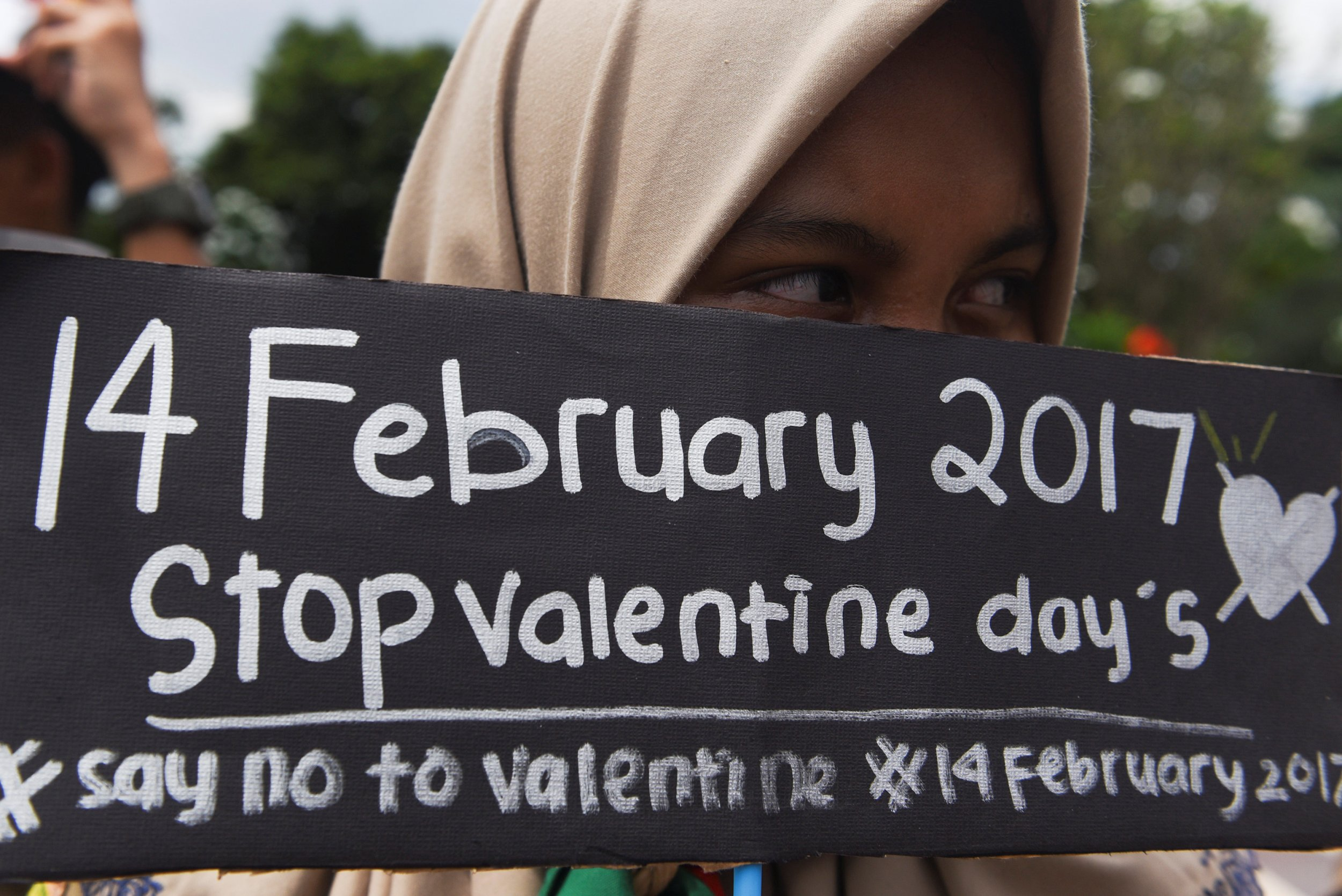 Girl holds up sign saying No Valentines