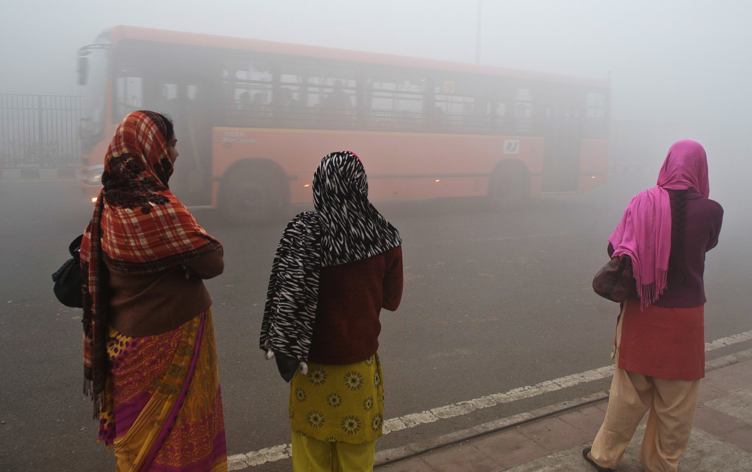 Women wait for bus in Delhi
