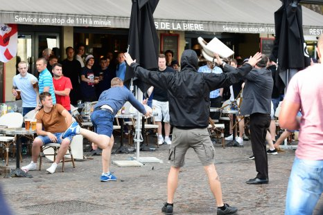 A Russia football supporter lobs a chair towards England fans sitting in a cafe in the northern city of Lille on June 14, 2016..