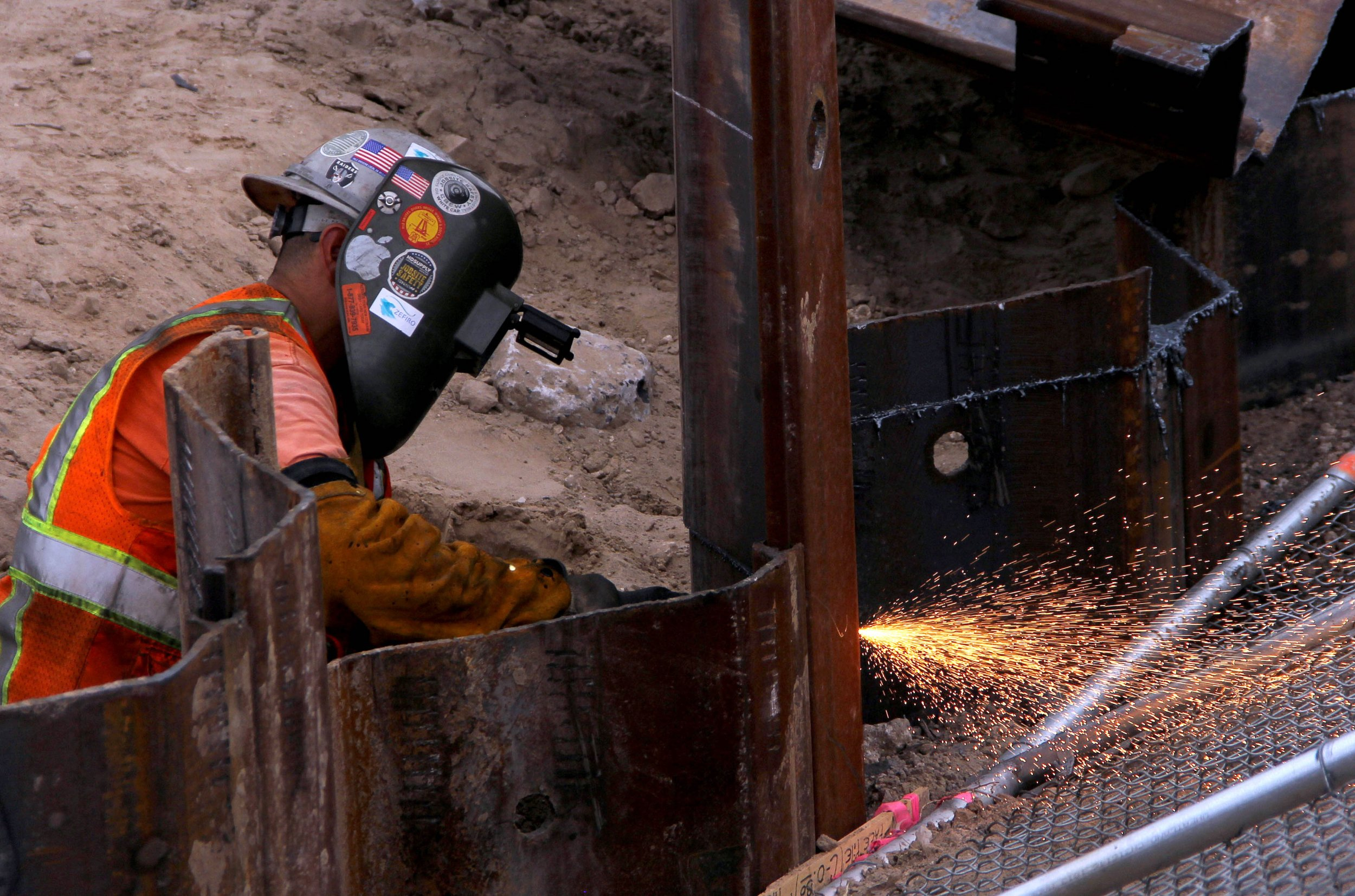 A man welds the Mexico-US border wall