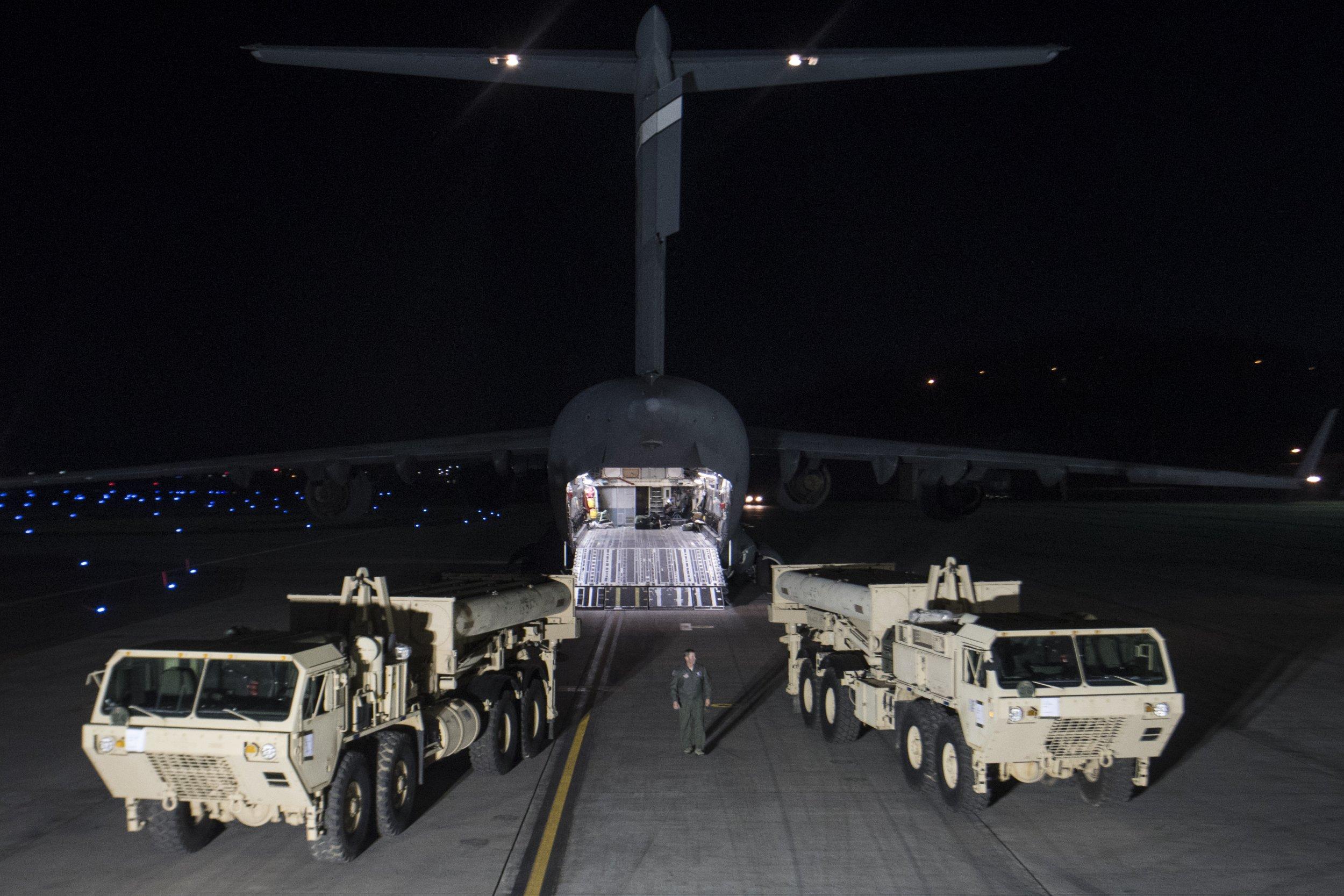 U.S. military trucks by a plane