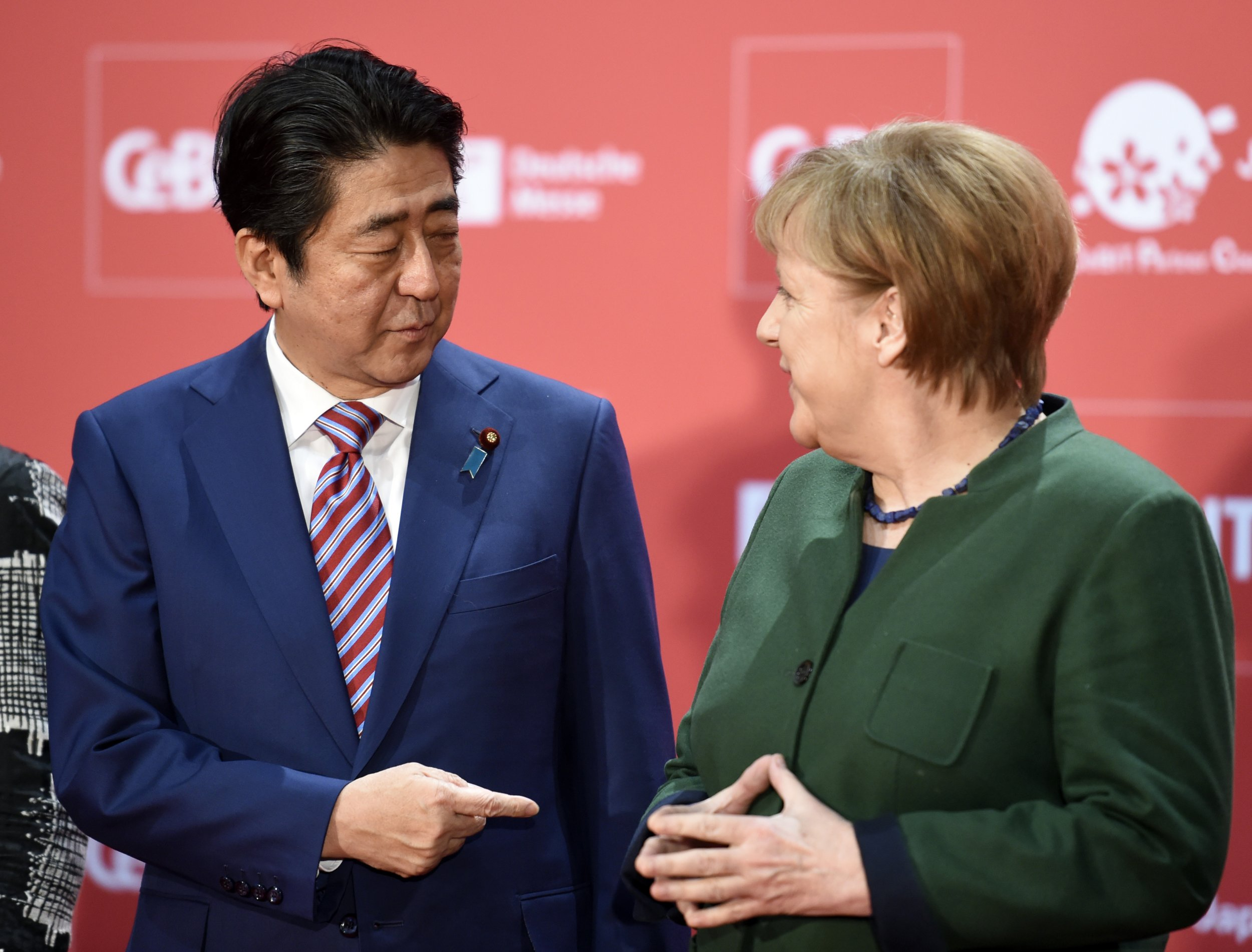 Germany's Angela Merkel and Japan's Shinzo Abe endorse free trade with jabs at Trump's rhetoric