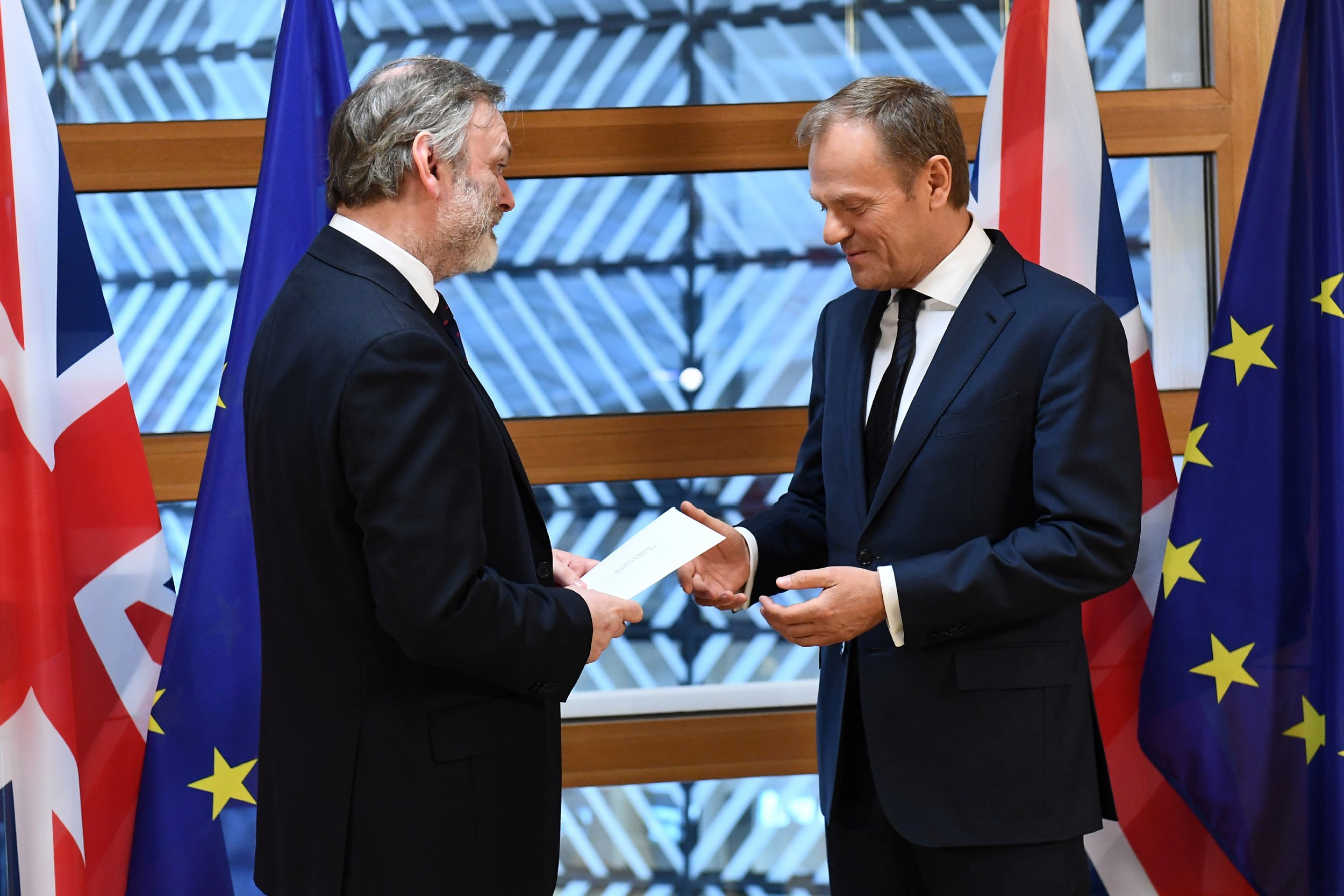 Britain's permanent representative to the European Union Tim Barrow, left, delivers British Prime Minister Theresa May's Brexit letter triggering Article 50 to Donald Tusk, right.