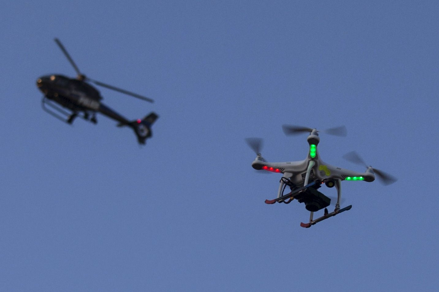 A Police Helicopter Flies Past UAV Drone Quadcopter Which Was Flying Over Post March Street Celebration In West Baltimore Maryland May 2 2015