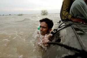 asia-fire-floods-pakistan-man-boat