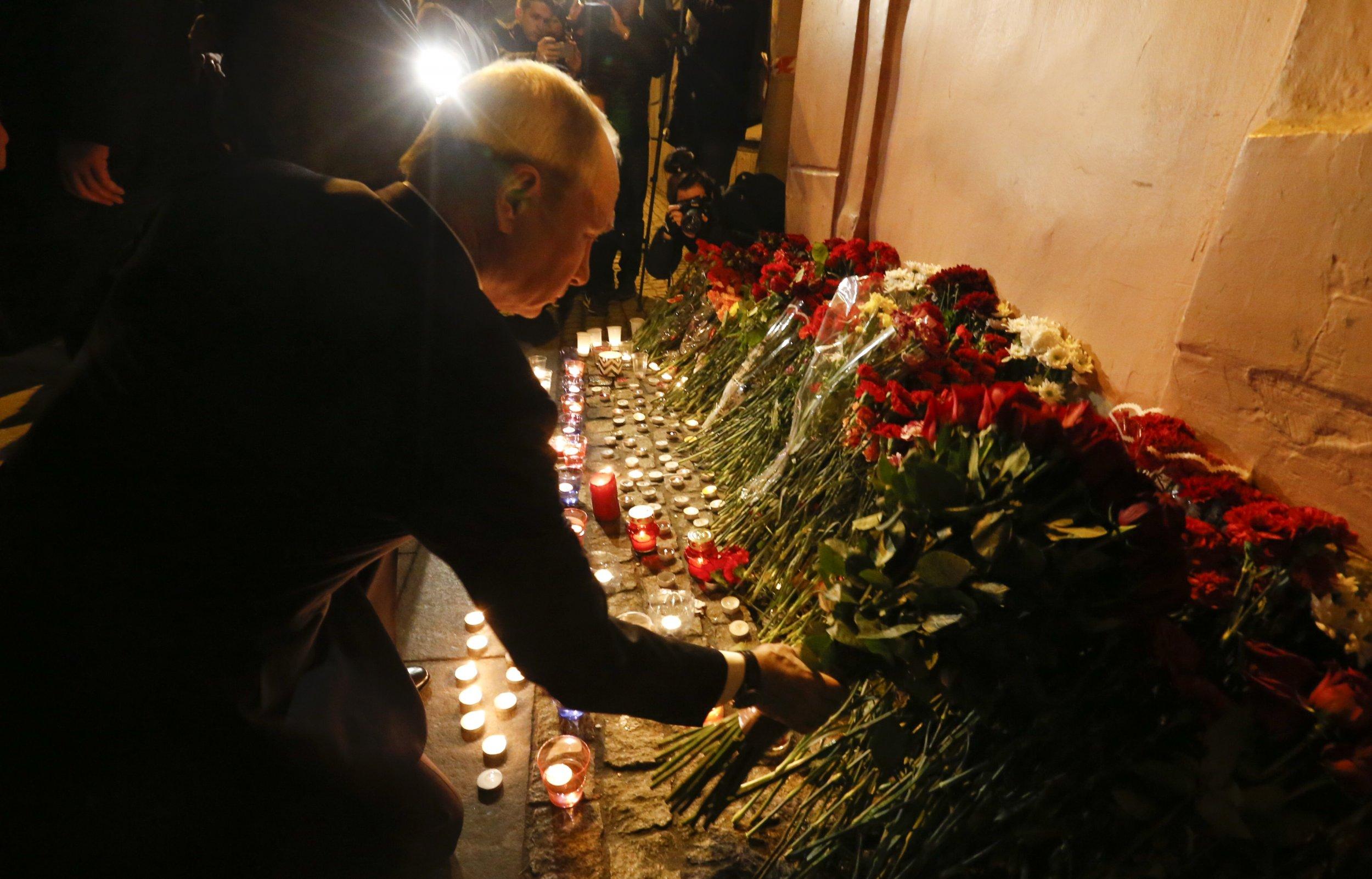 Russian president Vladimir Putin puts flowers down in St. Petersburg