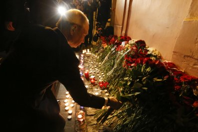 Russian president Vladimir Putin puts flowers down in St. Petersburg