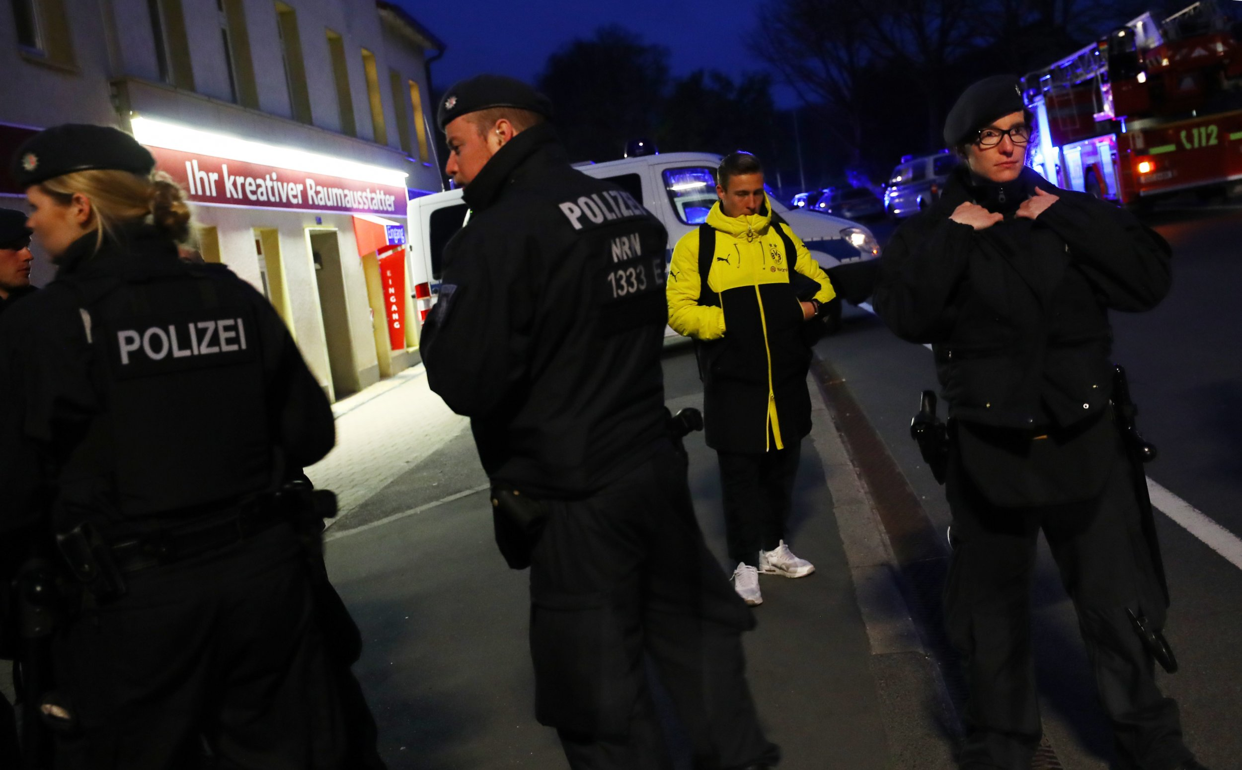 Borussia Dortmund's Felix Passlack with police after an explosion by the Borussia Dortmund team bus near their hotel in Dortmund, Germany, April 11.