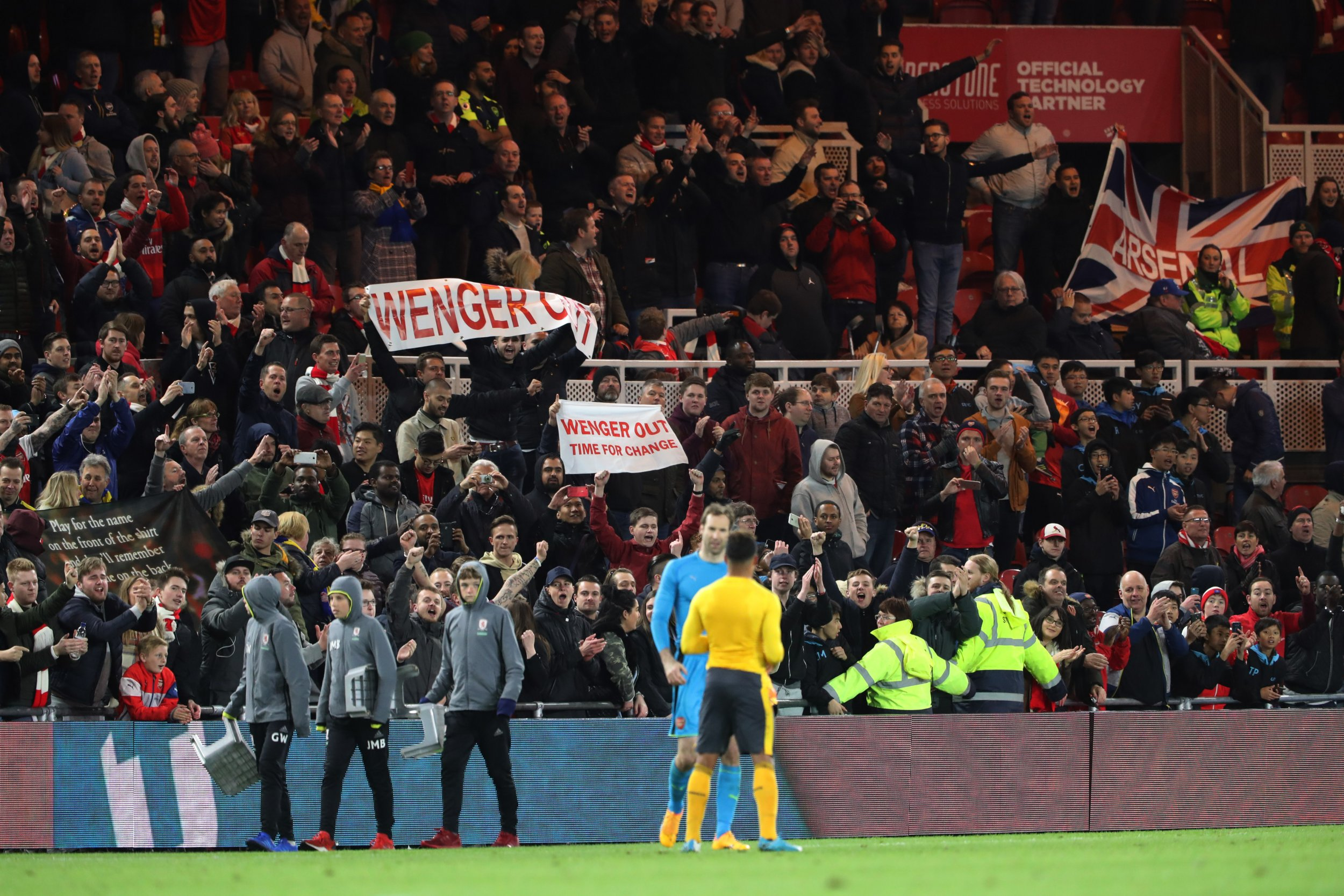 Arsenal fans hold up banners protesting against manager Arsene Wenger
