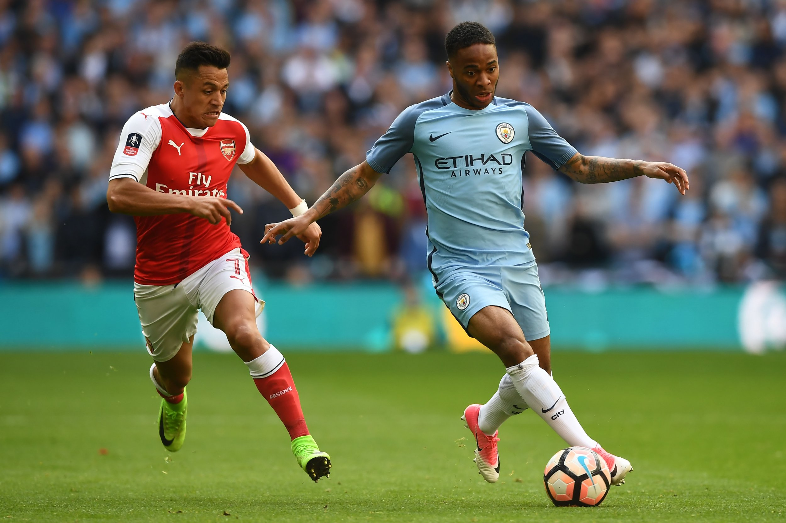 Manchester City winger Raheem Sterling, right, with Arsenal's Alexis Sanchez.