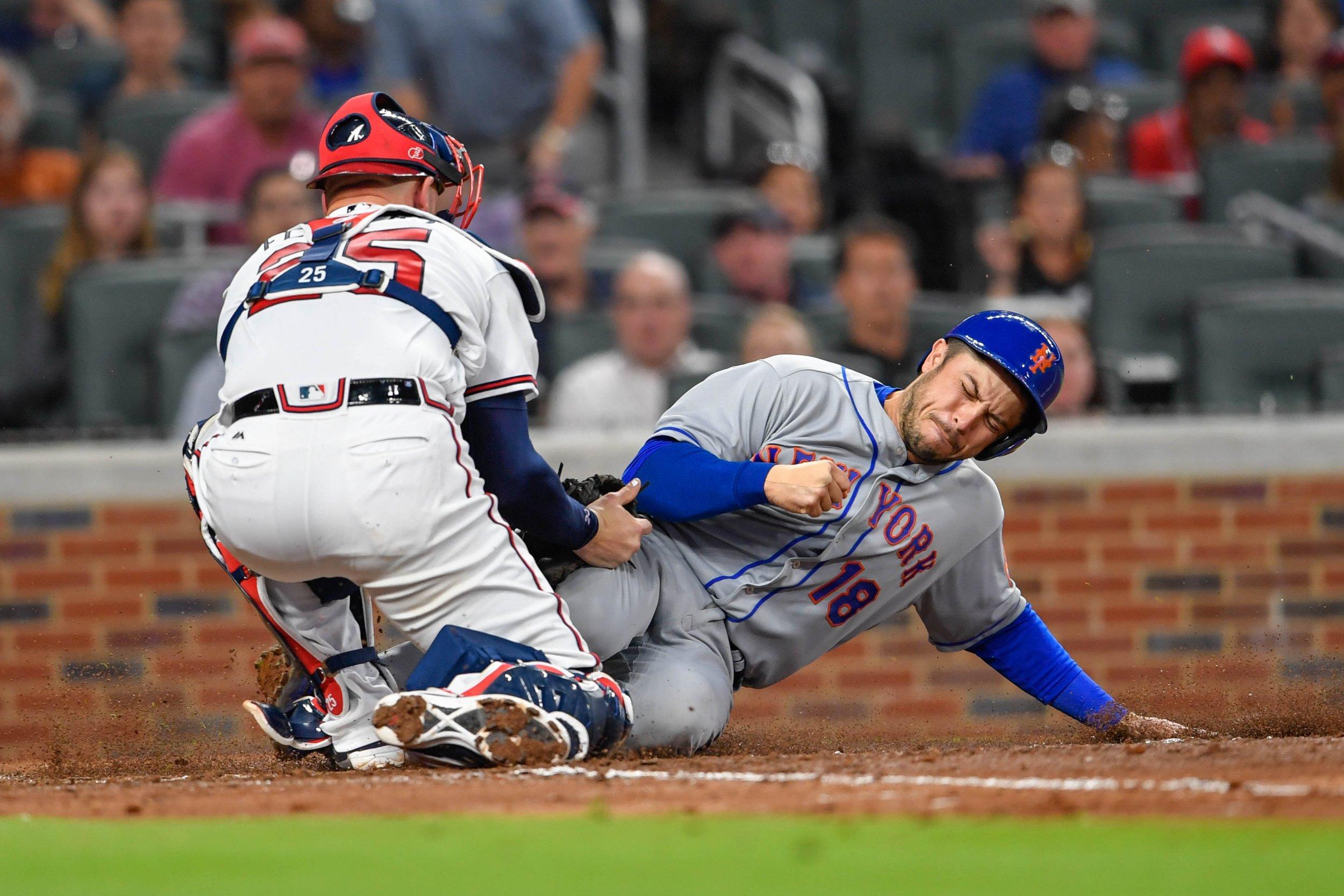 New York Mets catcher Travis d'Arnaud, right, slides under the tag by Atlanta Braves catcher Tyler Flowers at SunTrust Park, Atlanta, May 1 2017.