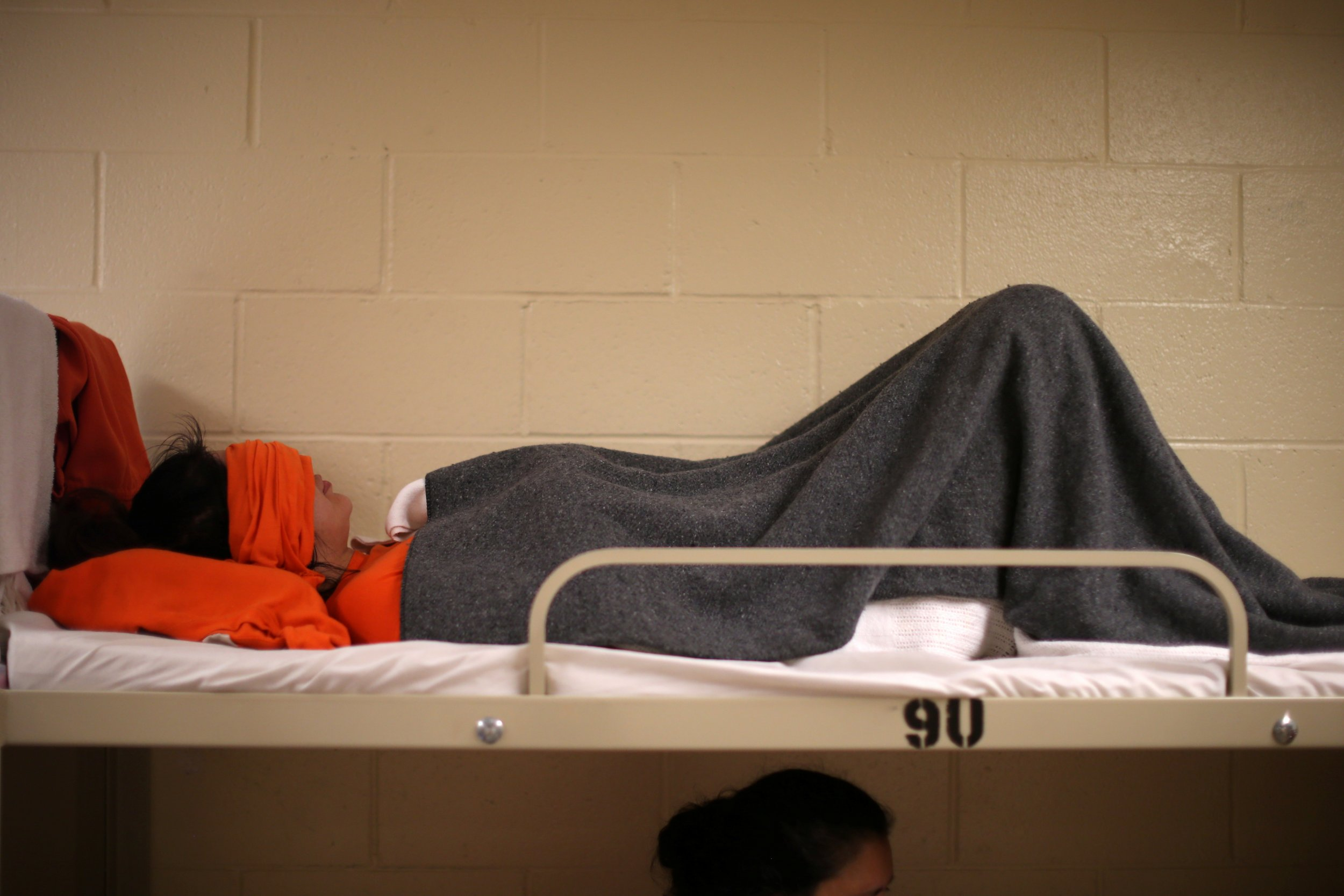 A woman lies on a bed at the Adelanto immigration detention center