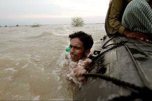 asia-fire-floods-pakistan-man-boat
