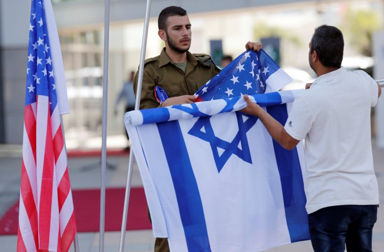 An Israeli soldier rolls up the flag of Israel