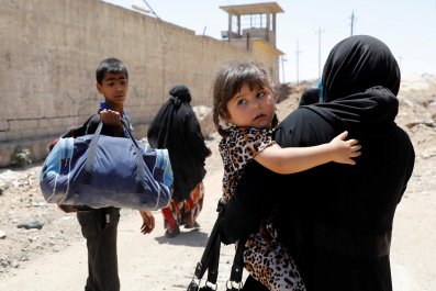 A woman carries a child in Mosul