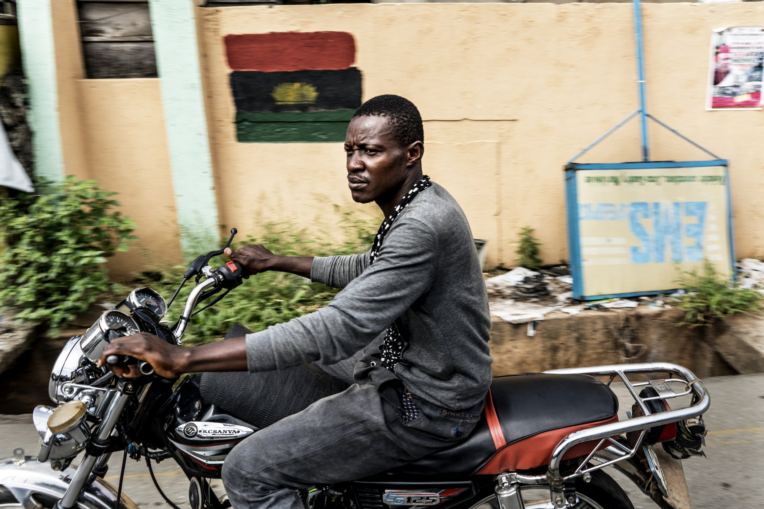 War in nigeria victory remains elusive 50 years on a man drives a motorbike past a biafran flag at the old market road in onitsha nigeria during a shutdown in commemoration of the 50th anniversary of the thecheapjerseys Images